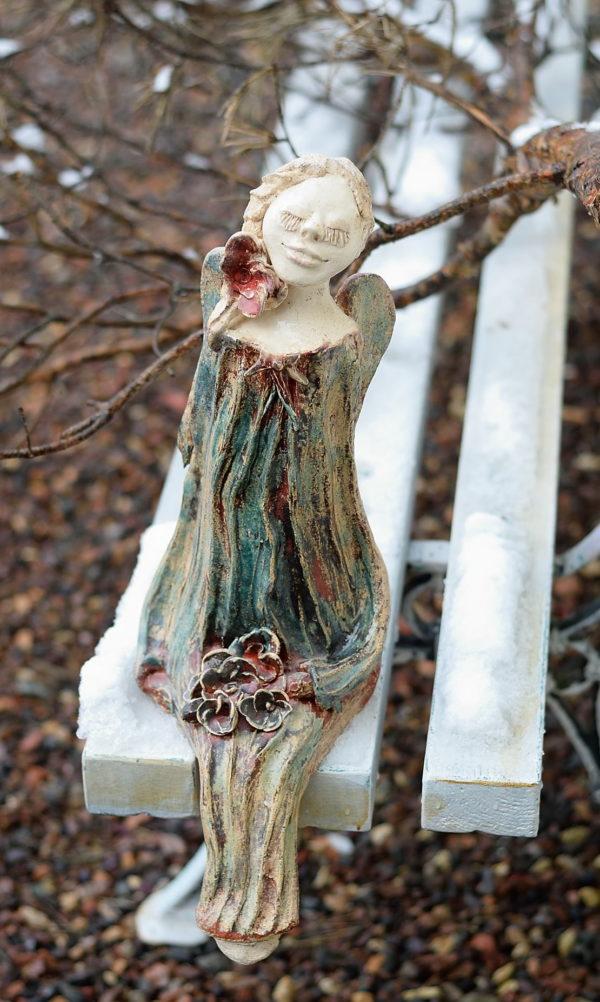 Duży ceramiczny anioł z kwiatami. Anioł z radosną miną. Siedzący anioł w czerwonym i niebieskim kolorze.
