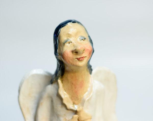 Biały anioł rzeźba ceramiczna. Ceramiczny anioł stojący w białym kolorze trzymający ptaszki wolności. Radosny, optymistyczny anioł.