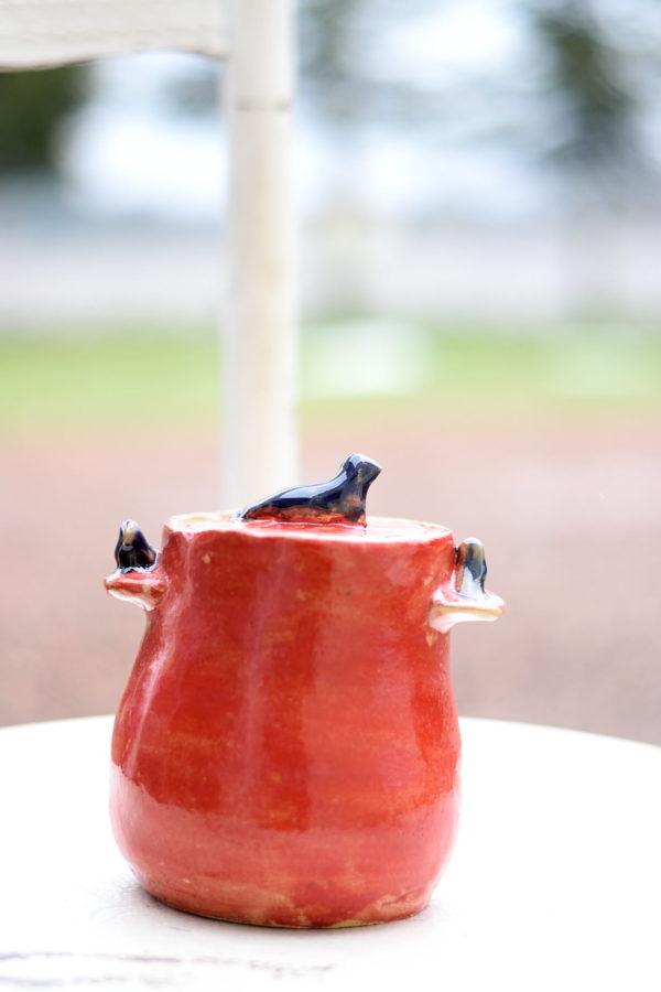 Ręcznie stworzony pojemnik na smalec. Ceramiczny garnuszek wykonany został z jasnej gliny. Pokryty został szkliwami do kontaktu z żywnością w kolorze czerwonym