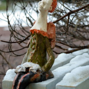 Ceramiczna rzeźba anioła trzymającego psa. Ceramiczny anioł w zielonym kolorze. Siedzący anioł na komodę