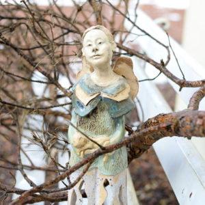 Ceramiczny lampion, duży ciekawy lampion na świeczkę. Przedstawia anioła trzymającego kota. Ażurowy spód na świecę. utrzymany w pastelowych kolorach
