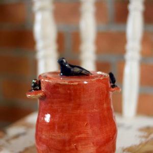 Ręcznie stworzony pojemnik na smalec. Ceramiczny garnuszek wykonany został z jasnej gliny. Pokryty został szkliwami do kontaktu z żywnością w kolorze czerwonym.